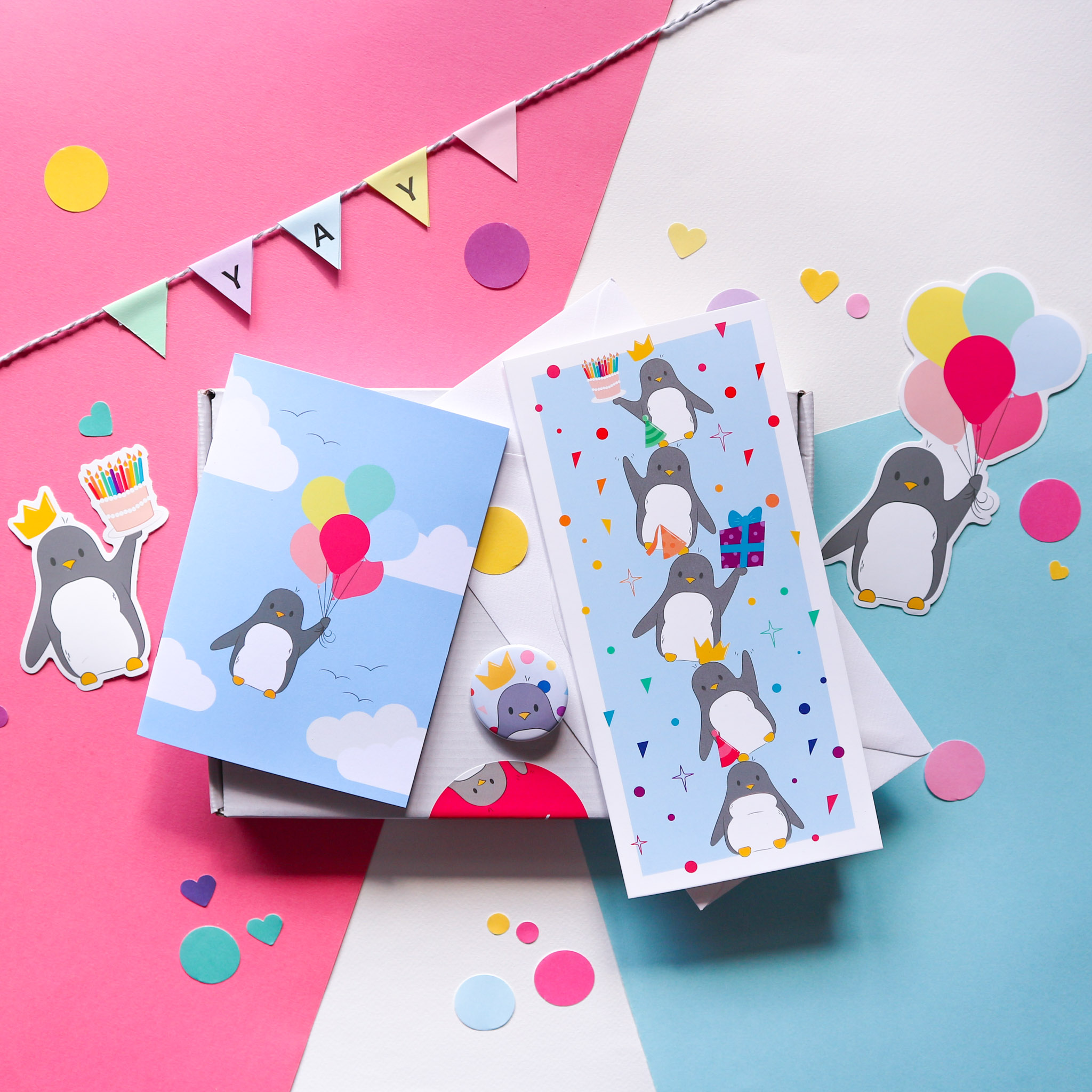 """Flatlay photograph of all the products in the birthday bundle box, two penguin birthday stickers (one holding a birthday cake, the other holding balloons), a little notebook with a penguin holding a bunch of balloons on the front, a string of paper saying """"yay,"""" a birthday card and a penguin birthday badge."""