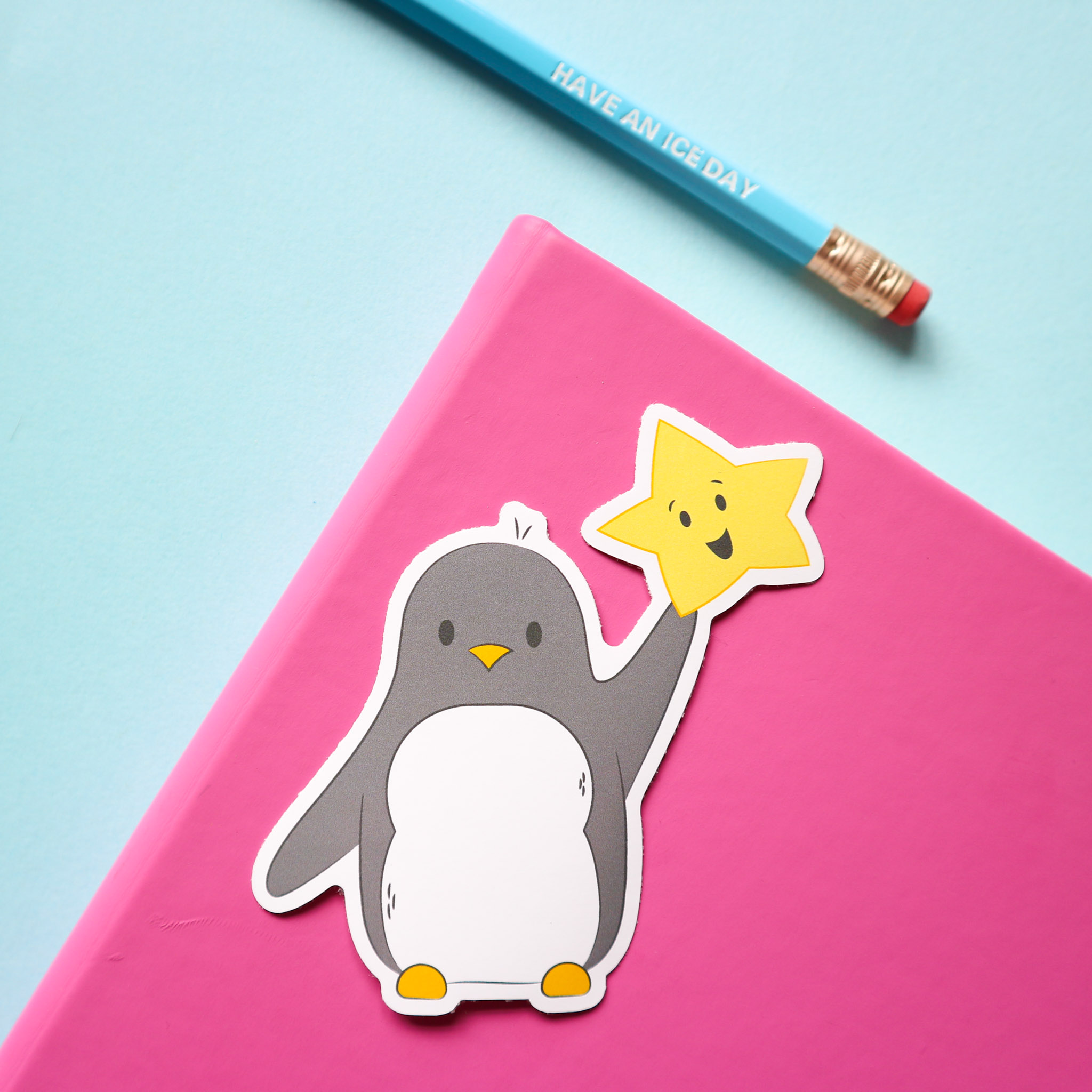 """sticker design of penguin holding a smiling star, against the background of a pink notebook, a pencil that say """"have an ice day"""" all on a pale blue background. Pencil not included in this listing."""