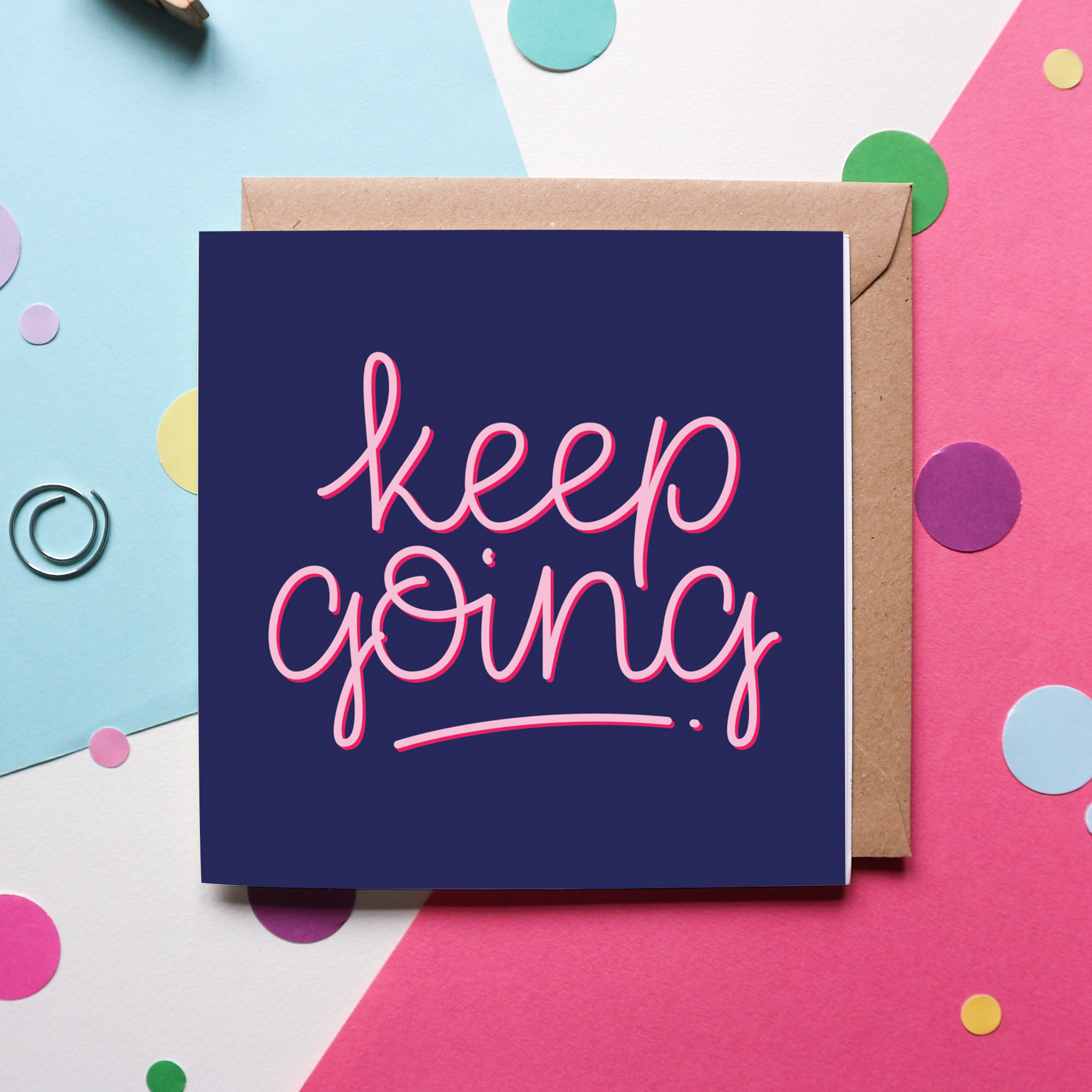 """A charming hand-lettered design that reads """"Keep Going"""" in pink cursive, against a navy blue background on a greeting card. The greeting card sits against a brown, kraft envelope and against a pink and blue background with colourful confetti and paperclips."""