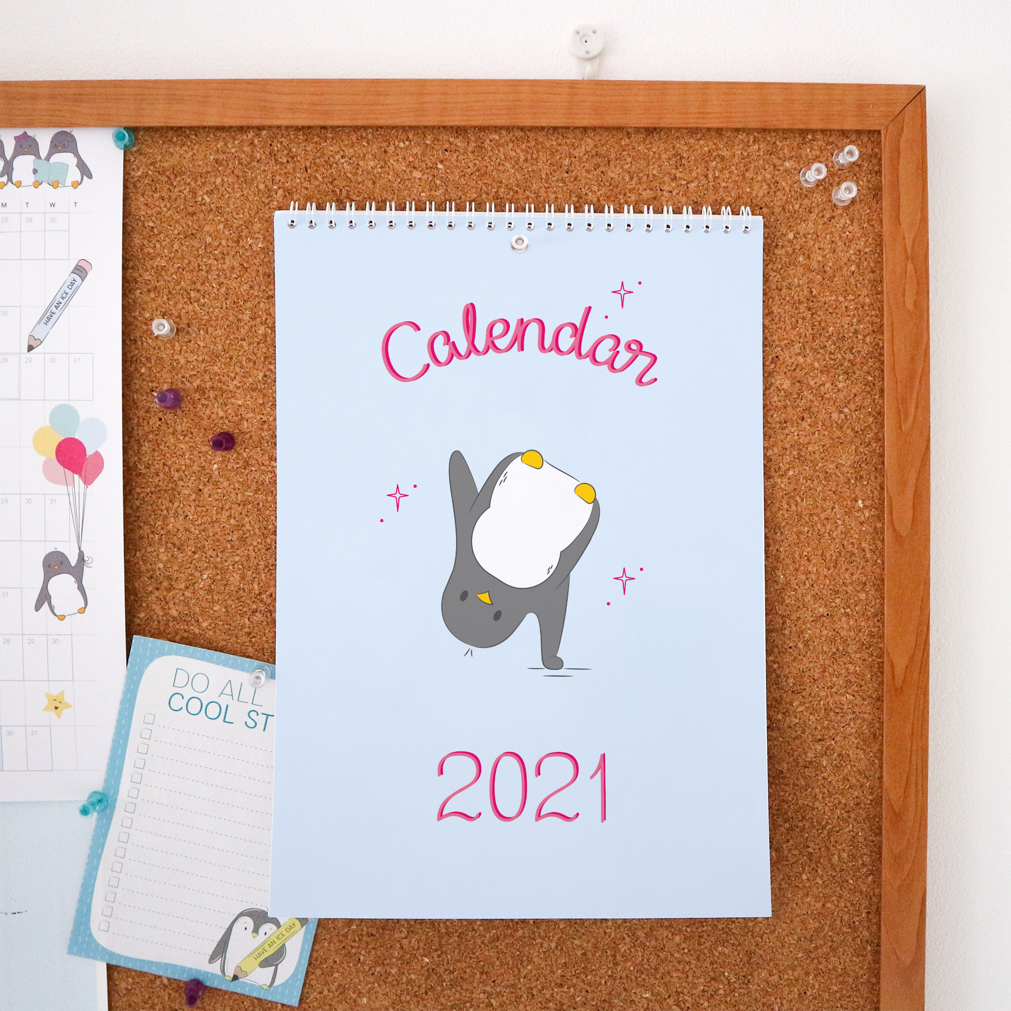 The front page of the 2021 calendar is an illustration of penguin cartwheeling, it has a pale blue background and the words calendar 2021 are hand-lettered in pink. This Calendar is wire bound A4 and is styled against a cork board background.