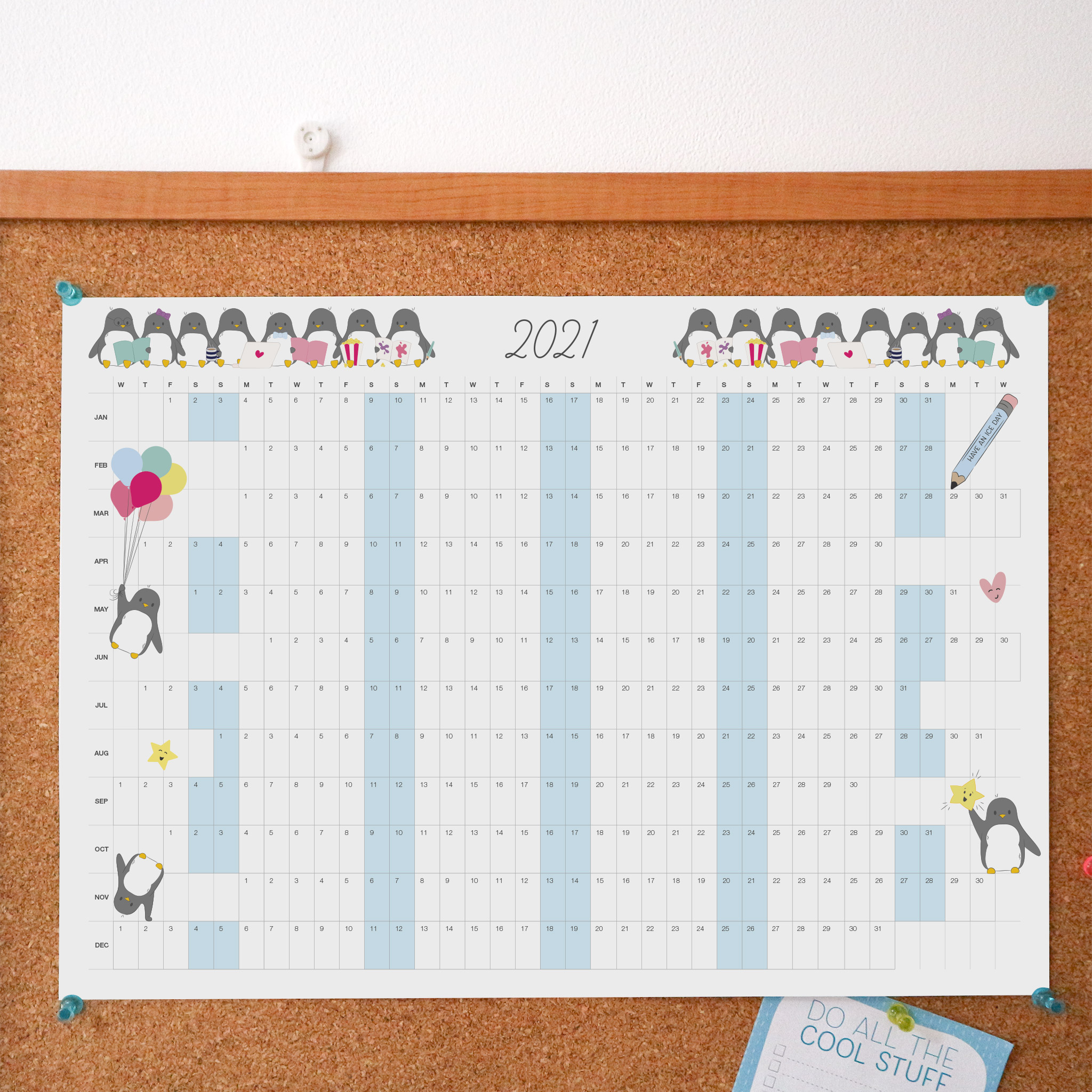 The 2021 year to view penguin wall calendar styled against a pin board background.