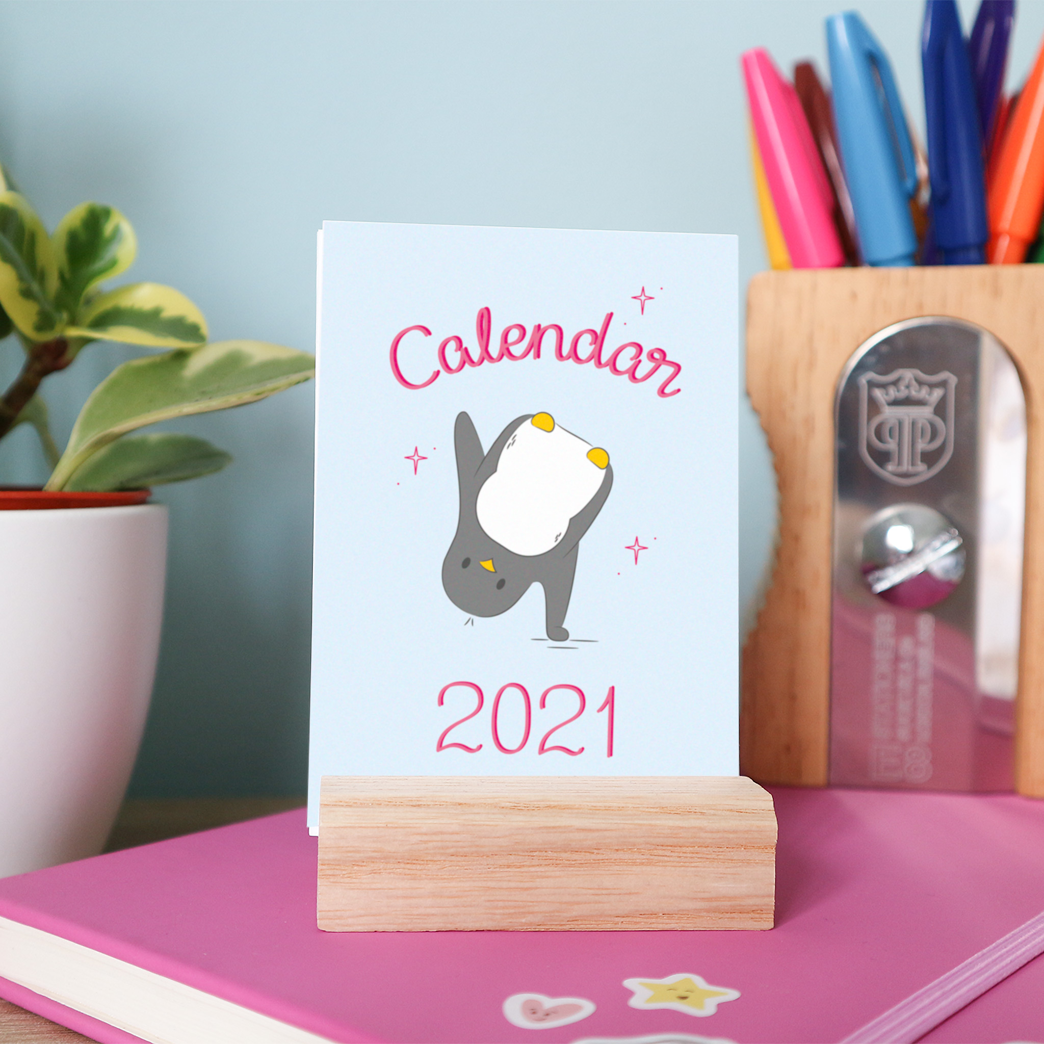 The front page of the 2021 calendar is an illustration of penguin cartwheeling, it has a pale blue background and the words calendar 2021 are hand-lettered in pink. The calendar is styled on the wooden stand, and in the background is a pencil pot and a leafy plant.